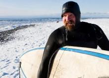 An Alaskan surfer walks over a snowy beach after a winter surf s