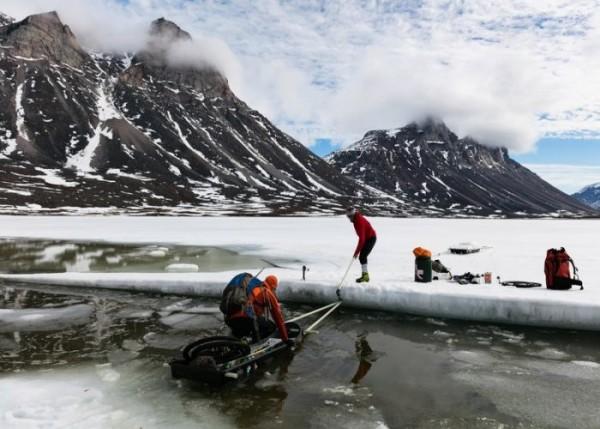 Überqueren von offenen Wasserstellen bei einem See, Stefan Glowacz, Robert Jasper und Fotograf Klaus Fengler auf dem Weg über den Revoir Pass zum Eglinton Fjord, Nunavut, Baffin Island, Kanada. Copyright: Klaus Fengler.